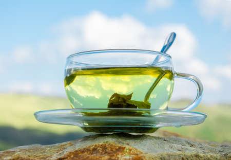 een Kop van groene thee op een achtergrond van bergen. Stockfoto