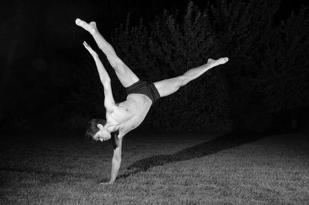 spread legs: male dancer on grass at night does a one hand, handstand