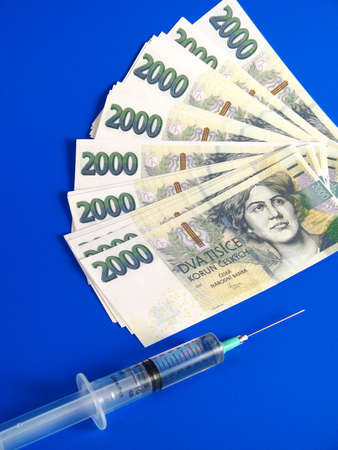 surgery expenses: Czech crowns and syringe over blue background Stock Photo