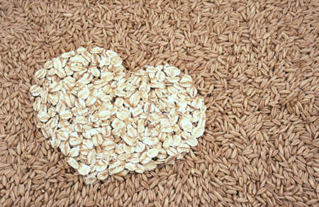 Oats seeds and oat-flakes heart - background Stock Photo