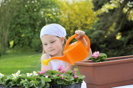 watering pot: Young girl watering flowers