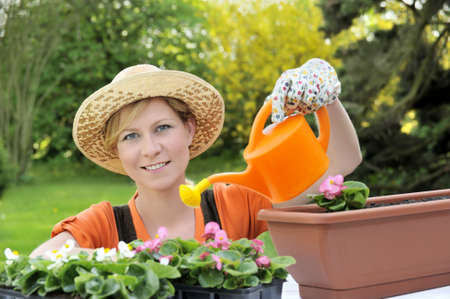 Young woman watering flowers photo