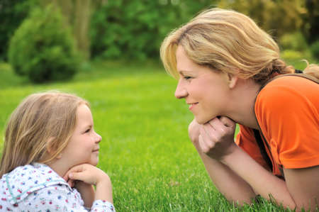 Young mother and daughter laying on the grass Stock Photo - 5815463