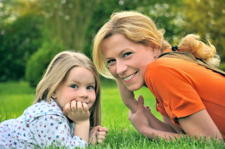 Young mother and daughter laying on the grass Stock Photo - 5815466