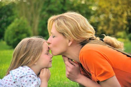 personas besandose: Madre es besando a su hija