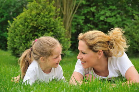 Young mother and daughter laying on the grass Stock Photo - 5886511