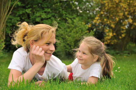 Young mother and daughter laying on the grass Stock Photo - 5890761
