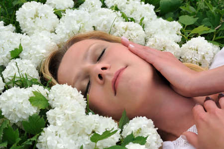 Young woman laying in flowers - snowballs photo