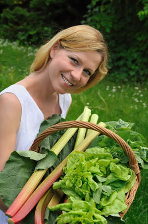 Young woman holding basket with vegetable Stock Photo