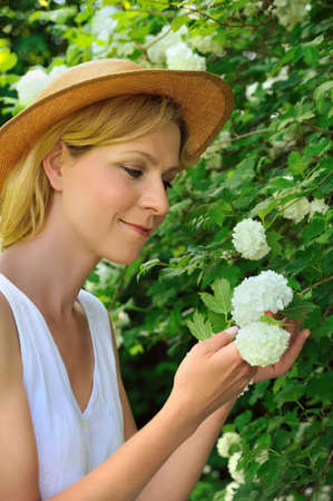 floriculturist: Young woman gardening - taking care of snowball