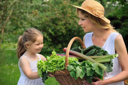 Young woman and daughter with fresh vegetable photo