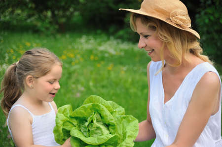 green leafy vegetables: Young mother and daughter with lettuce