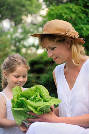 Young mother and daughter with lettuce photo