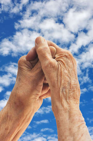 pleading: Senior womans hands over sky
