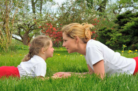 Young mother and daughter laying on the grass photo