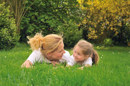 Young mother and daughter laying on the grass Stock Photo - 6979815