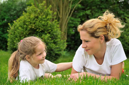 Young mother and daughter laying on the grass Stock Photo - 6979814