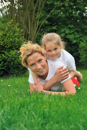 Young mother and daughter laying on the grass Stock Photo - 6979809