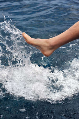 Foot of young man in water - splash photo