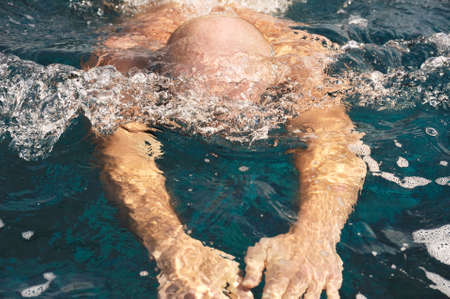 Detail of young man swimming photo