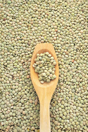 Wooden spoon and dried green lentils photo