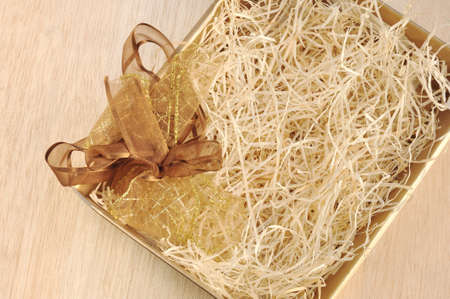 Open gift box and bow - filled with packing bast photo