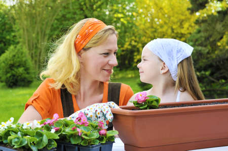 Young mother and her daughter - gardening photo
