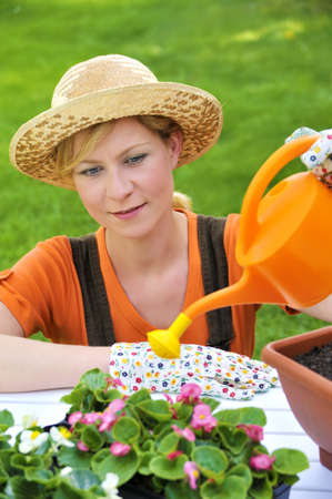 floriculturist: Young woman watering flowers