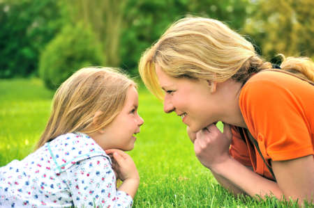 age 30 35 years: Young mother and daughter laying on the grass Stock Photo