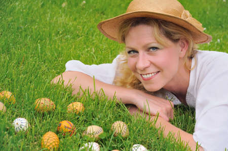 boater: Young woman and easter eggs on the grass - Easter time