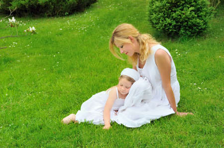 Young mother and daughter resting in meadow photo