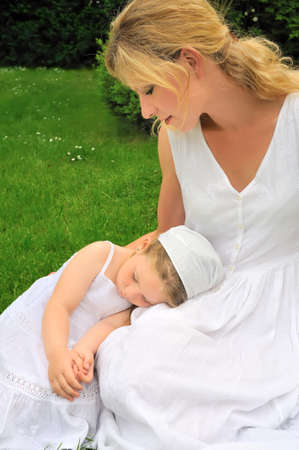 day dreaming: Young mother and daughter resting in meadow