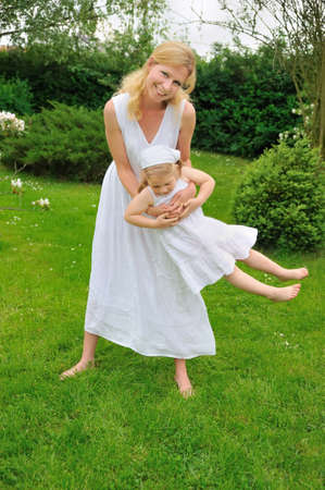 Young mother and daughter playing in meadow photo
