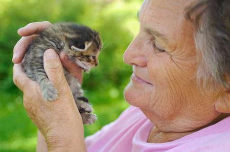 Senior woman holding kitten photo