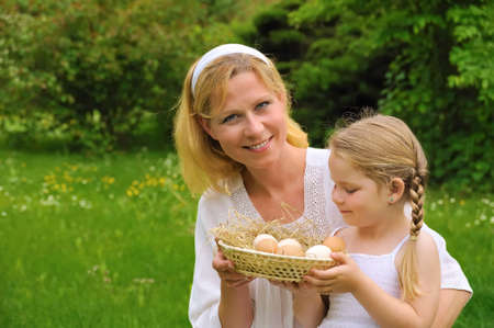 Mother and daughter holding fresh eggs photo