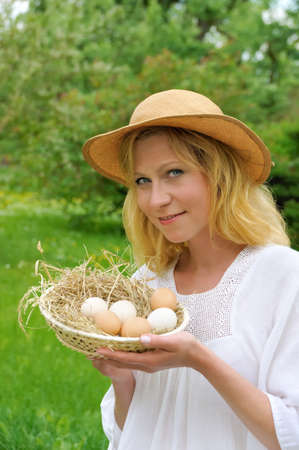 Young woman holding fresh eggs photo