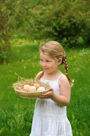 Little girl holding fresh eggs photo