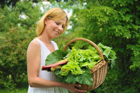 green's: Young woman holding basket with vegetable Stock Photo