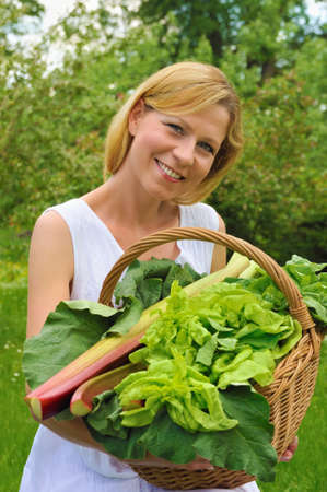 rhubarb: Young woman holding basket with vegetable Stock Photo