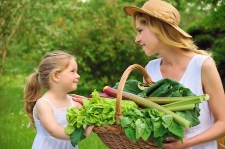 farming village: Young woman and daughter with fresh vegetable