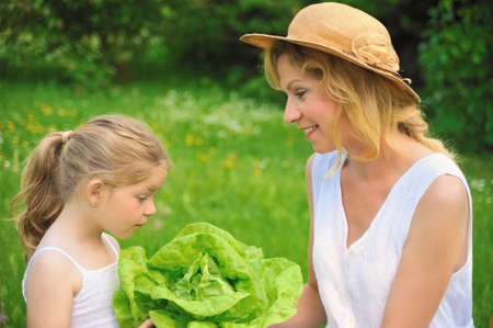family gardening: Young mother and daughter with lettuce