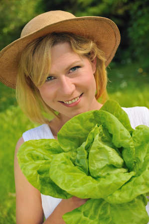 one year: Young woman holding fresh lettuce