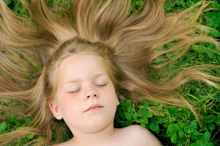 Little girl laying on the grass photo