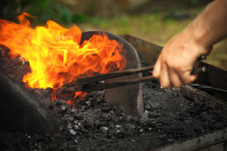 medieval blacksmith: Blacksmith heating up iron - detail Stock Photo
