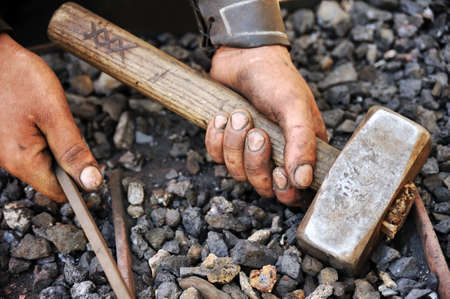 Detail of dirty hands holding hammer and rod - blacksmith photo