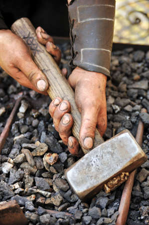 Detail of dirty hands holding hammer - blacksmith Stock Photo - 9923474