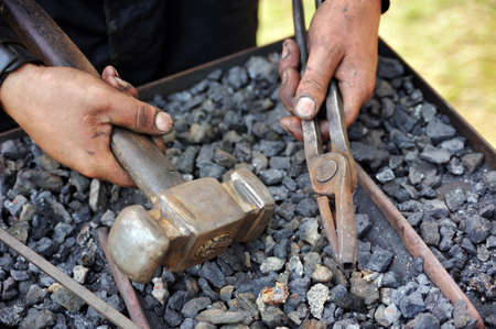 Detail of dirty hands holding hammer and pliers - blacksmith Stock Photo - 9923475