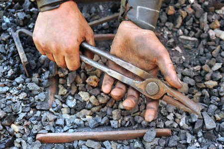 Detail of dirty hands holding pliers - blacksmith Stock Photo - 9923479