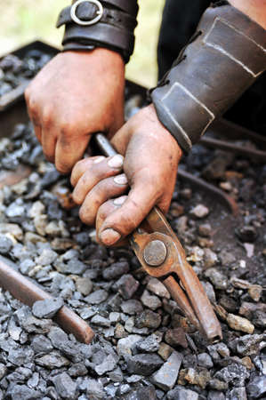 Detail of dirty hands holding pliers - blacksmith Stock Photo - 9923473