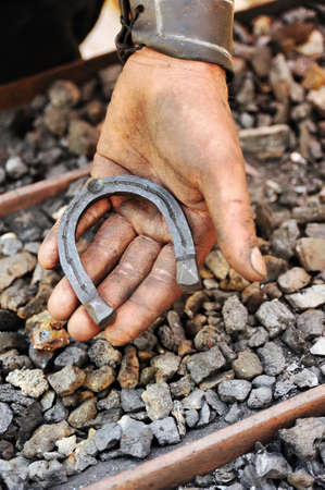 Detail of dirty hand holding horseshoe - blacksmith Stock Photo - 9923478